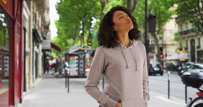 African American woman on street corner tilts head back to feel the sun and wind