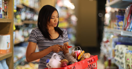 Young black woman at the grocery store picking things up for dinner