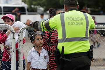 A Colombian policeman stand in front of people who are trying to cross into Venezuela from Colombia via the Simon Bolivar international bridge in Cucuta