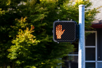 Crosswalk hand symbol sign on a post