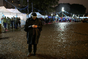 An anti-abortion rights activist prays as lawmakers are expected to vote on a bill legalizing abortion, in Buenos Aires