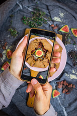 Phone food photography. Smartphone photo of food during lunch or dinner. Blogging and social media food photo on mobile camera. Trendy food shot. Vegan sweet figs tart dessert