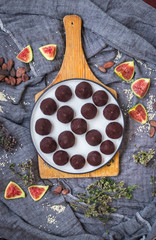 Chocolate truffle confectionary made with grated chocolate, cocoa or carob powder, coconut oil, chopped nuts, sweet nuts. Healthy vegan sweets or vegetarian sweets.