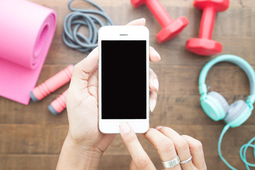 Hands using phone black screen on top view with fitness equipments, Healthy and Lifestyle concept