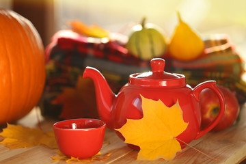 Autumn tea.red teapot with a cup of tea,  stack of checkered scarves,  yellow autumn leaf and a pumpkin on a wooden table on a blurry light background.Autumn season.