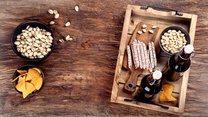 Beer and snacks on wooden background