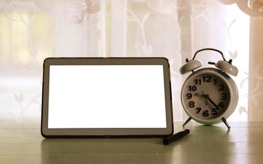 Home working desk interior blur window in morning background with white screen tablet and alarm clock on table