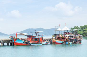 colorful Thai wooden fishing boats floating moored in coast at Koh Chang island and Trad province, Thailand