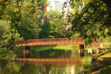 Landscape of the park with a lake, a bridge and a house in the background