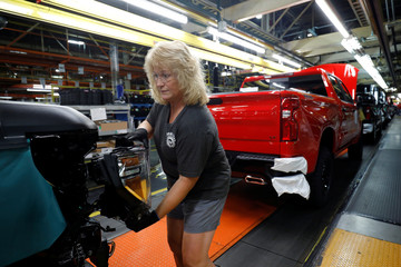 Kathy Huff installs a headlight assembly at GM's Chevrolet Silverado and GMC Sierra pickup truck plant in Fort Wayne Indiana