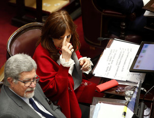 Senator and former Argentine President Cristina Fernandez de Kirchner sits next to Senator Marcelo Fuentes as lawmakers debate on a bill that would legalize abortion, in Buenos Aires