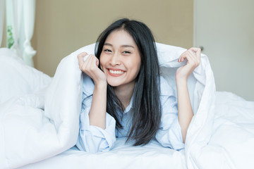 Sleeping Asian beauty woman looking out of under white blanket. Sweet dreams in tender bed in bedroom. Beautiful female eye in a whisper tells secrets. Good morning (night) or sweet dreams
