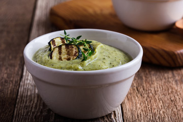 Healthy zucchini cream soup in ceramic bowls