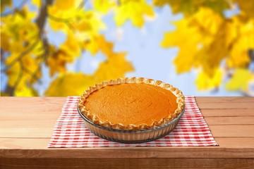Home made pumpkin pie on autumn background