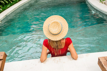 Back of a beautiful young female in sexy red swimsuit and vintage straw hat posing in blue pool water. Hot sunny day. Tropic island vacation hotel. Summer travel girl, active hipster lifestyle.