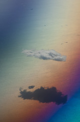 Solitary cloud in the north of the Aegean sea saw from an airplane. Colors produced when light is passed through the airplane window.