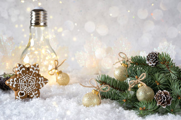New Year's decoration. Christmas tree branch with balls on snow background and beautiful lamp light with home cookies. Copy space