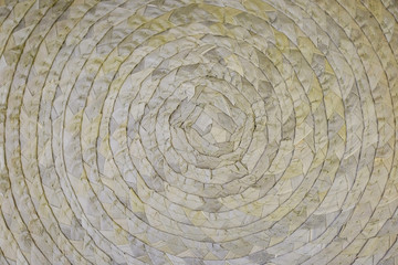 A woven Mat of reeds or straw-yellow in color. The texture of dry cane. Dark yellow.