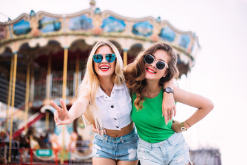 Closeup fashion lifestyle portrait of two pretty best friends girls, wearing bright swag style floral hats, mirrored sunglasses, having fun and make crazy funny faces.