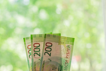 new russian banknotes against green bokeh background. two hundred roubles. Cash paper money.