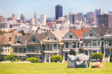 San Francisco - Alamo Square people. Couple tourists relaxing in Alamo Park by the Painted Ladies houses iconic landscape, The Seven Sisters, San Francisco, California, USA.