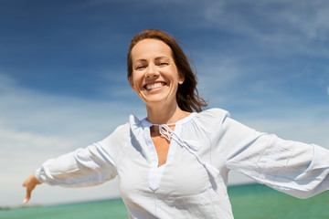 people and leisure concept - happy smiling woman on summer beach