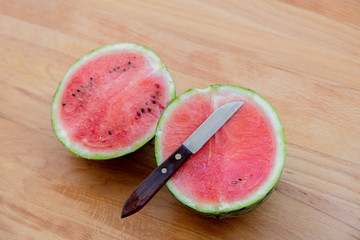Watermelon and knife on wooden table. Above view