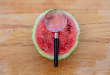 magnifier and cut watermelon on wooden table. Above view