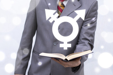 Transgender Learning concept. Young man holds book with transgender (combining gender) symbol icon on a virtual interface.
