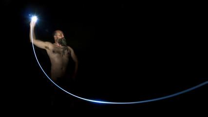 man sending a flash light in the dark