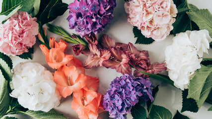 top view of colorful hydrangea and gladioluses flowers on marble surface