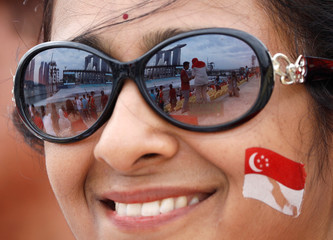 A spectator waits for the National Day parade along Marina Bay in Singapore
