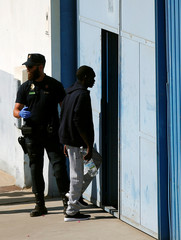 A migrant is led by Spanish police officers into the new Center for Temporary Assistance to Foreigners after arriving at the port of Algeciras in San Roque