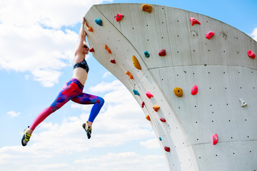 Photo of sportswoman in leggings hanging on wall for rock climbing against blue sky