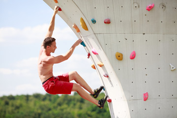 Photo of young man exercising on wall for climbing against cloudy sky