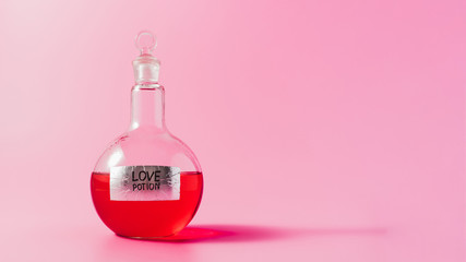 close-up shot of flask with red colored love potion on pink surface