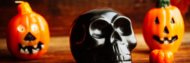 human skulls and pile of withered dry flowers and candle light on black fabric texture on dark background in night time / Still life image and Selective focus, the format of the banner, wide long