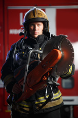 Photo of serious fireman wearing helmet with chainsaw on background of fire engine