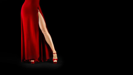 unrecognizable sexy female legs in a red dress and high heeled shoes on a black background.