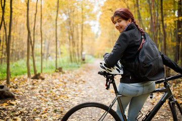 Photo of smiling brunette in jeans next to bicycle