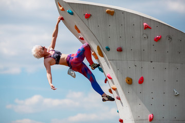 Photo of sportive girl on workout on climbing wall