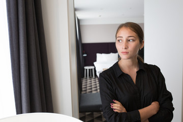 Fototapeta a young girl with gathered hair in a black shirt and skirt stands at the entrance to the bedroom with a white door,