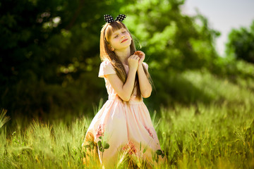 Portrait of beautiful little girl in elegant dress in middle of green summer field