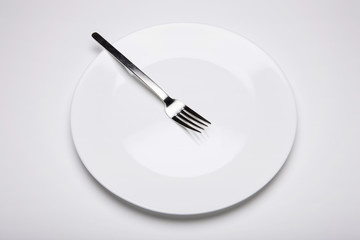 empty white dish with a fork on the white bottom.