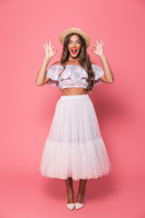 Full length portrait of adorable glamour woman 20s wearing straw hat and fluffy skirt showing ok sign, isolated over pink background in studio