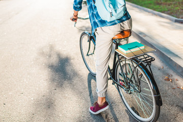 partial view of student with backpack riding bicycle on street