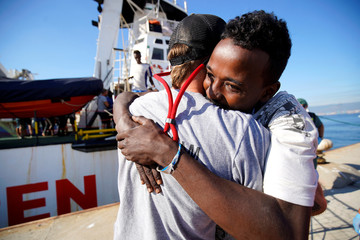 A migrant rescued by NGO Proactiva Open Arms rescue boat in central Mediterranean Sea embraces Open Arms Head Mission, Riccardo Gatti, after arriving at the port of Algeciras in San Roque