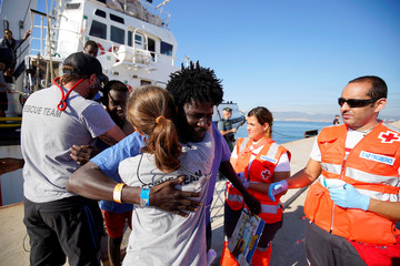 Migrants rescued by NGO Proactiva Open Arms rescue boat in central Mediterranean Sea embrace Open Arms members after arriving at the port of Algeciras in San Roque