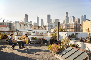 Couple Drinking Wine And Making Toast On Rooftop Terrace With City Skyline In Background
