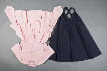 on a gray surface lined with a pink blouse and blue skirt, women's clothing, the concept of fashion and shopping